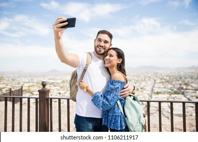 Happy young man and woman taking self portrait with city scenery in background during day