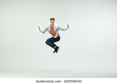 Happy young man working at office, jumping and dancing in casual clothes or suit isolated on white studio background. Business, start-up, working open-space, ballet or professional occupation concept.