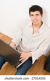 Happy young man working on his laptop with casual clothing