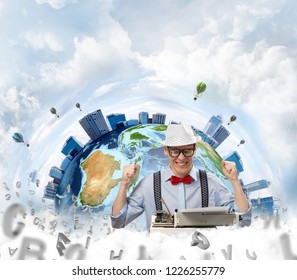 Happy and young man writer in hat and eyeglasses looking happy while sitting with typing machine at the table with flying letters and Earth globe among cloudy skyscape on background. Elements of this