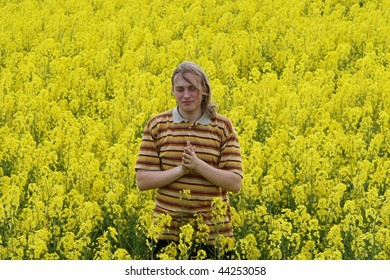 Happy young man in the yellow flower meadow.