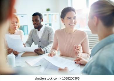 Heureuse jeune directrice ou comptable regardant sa collègue avec le sourire pendant la conversation