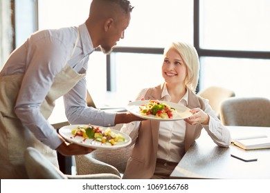 Happy young manager taking plate with her order in cafe and saying thanks to waiter
