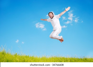 Happy young mane in white jumping on beautiful meadow