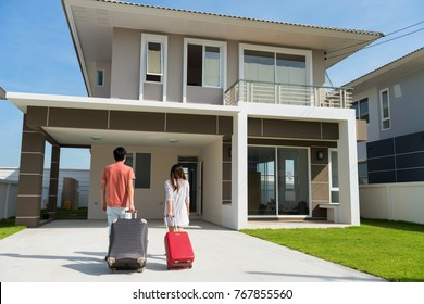 Happy Young married Asian male and female couple moving in a new modern house. Husband and wife pull luggage and walk to home door entrance. Family lifestyle They bought first home together. New life