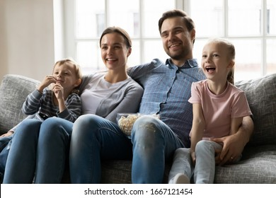 Happy young married couple embracing little kids siblings, watching funny movies or tv show, eating popcorn, resting on sofa. Smiling family enjoying weekend time with small kids in living room.