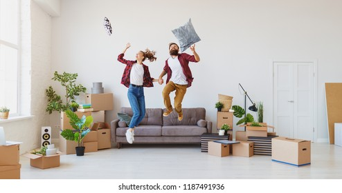 a happy young married couple moves to new apartment and laughing,  jump, fight pillows