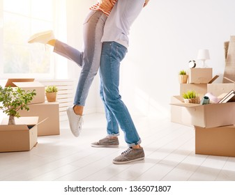 Happy young married couple are moving to new apartment.