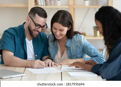 Happy young married couple signing contract, making successful deal, smiling young husband wearing glasses putting signature on legal documents, purchasing new house, taking loan or mortgage
