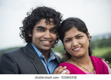 Happy young married indian couple laughing and looking at camera.