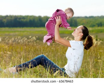 Happy young mather play with smiling baby and throw upwards on nature