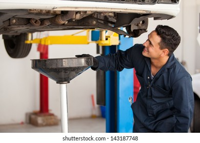 Happy young mechanic changing the oil of a car at an auto shop