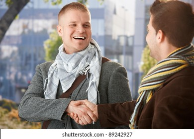 Happy young men shaking hand in greeting, laughing, standing outdoors in trendy clothes.?