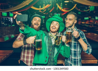 Happy young men taking selfie together in pub. Guy in middle wear St. Patrick's suit and hold phone in hands. They smile.