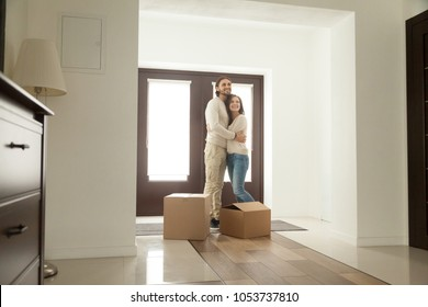 Happy young millennial couple hugging standing near boxes moving into new home, smiling homeowners embracing in modern hallway just moved in own house, mortgage investment and relocation concept