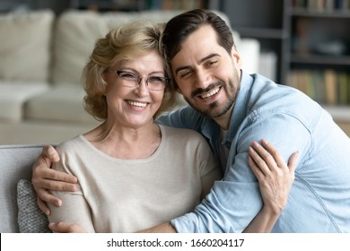 Happy young millennial man hug optimistic mature mom show gratitude relaxing at home together, thankful grown-up adult son embrace middle-aged mother express love and care, family bonding concept