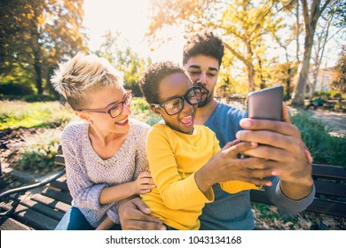 Happy young mixed race couple spending time with their daughter using smart phone in public park