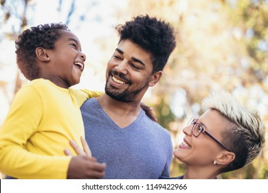 Happy young mixed race couple spending time with their daughter having fun