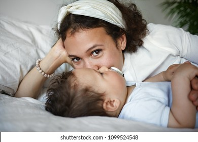 Happy young mixed race female relaxing indoors, lying in bed with her adorable baby toddler, kissing him on cheek and looking at camera with joyful facial expression. Love, family and childcare