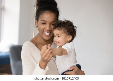 Happy young mixed race mother holding funny little infant kid on hands, enjoying playtime activity together indoors. Affectionate loving african ethnicity mum having fun with adorable small baby.