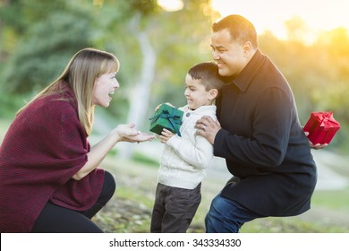 Happy Young Mixed Race Son Handing Gift to His Mom As Father Stands Behind.