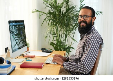 Happy young mixed-race it-engineer looking at you with smile while searching in data base by workplace