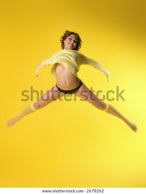 Happy young model jumping high on yellow