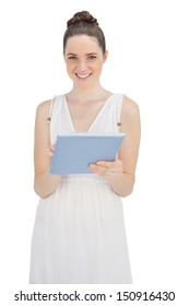 Happy young model in white dress on white background holding tablet computer