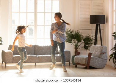 Happy young mom and cute little daughter jumping dancing in modern house living room, joyful mother with child girl having fun enjoy moving to music together at home, mum and kid funny activity