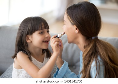Happy young mom and cute preschooler daughter have fun together at home paint lips with lipstick, excited nanny or sister entertain do makeup with small girl child, enjoy spend time at home