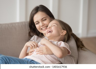 Happy young mom and funny little daughter have fun lying relaxing on couch at home, smiling mother or nanny enjoy spending time with small preschooler girl laughing and giggling playing together