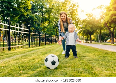 Happy young mom and her little son play soccer together outdoors in the park