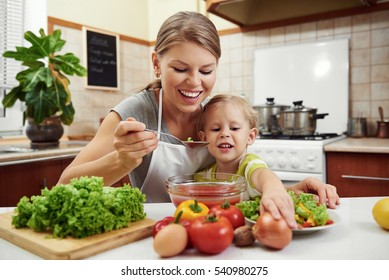 Happy young mom with little girl preparing tomato sauce in the kitchen at home. Concept of lifestyle and healthy food.