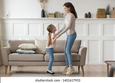 Happy young mom or nanny have fun hold hands dancing with little funny girl child, excited mother entertain laugh jumping in living room with smiling preschooler daughter, enjoy time at home together