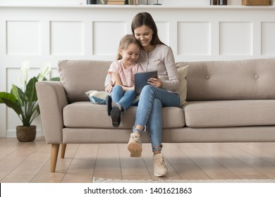 Happy young mom or nanny sit on couch relax with little daughter watch cartoon on tablet together, smiling mother and preschooler girl child have fun using playing on pad resting at home