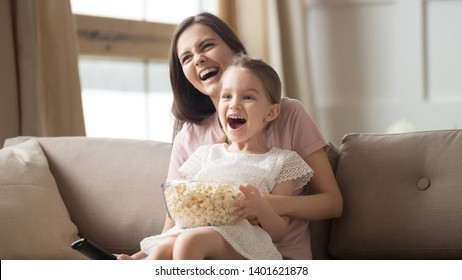 Happy young mom sit holding excited little daughter eating popcorn watch cartoon on TV together, smiling mommy or nanny have fun relaxing with small girl child enjoy movie or video with snack at home