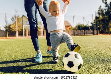 Happy young mom with son play soccer on the field, outdoors