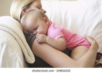 Happy young mother with baby boy lying on sofa at home