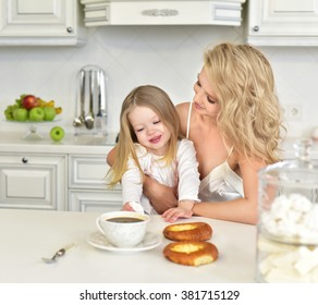 Happy young mother with a baby in the kitchen interior.