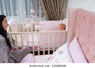A happy, young mother and baby in a pink bedroom scene with crib.