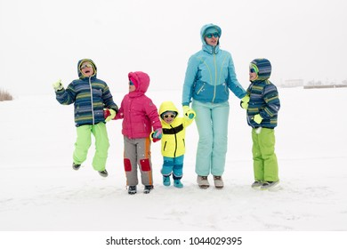 Happy young mother in blue ski suit wearing sunglasses with funny children in bright winter clothes jumping for joy on shore of icy lake. Wonderful winter vacation for whole family. Kids fun together