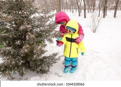 Happy young mother in blue ski suit wearing sunglasses with funny children in bright winter clothes, walking holding hands in park. Wonderful winter holidays for whole family. Children fun together