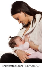 A happy young mother is breastfeeding her baby daughter on a white background
