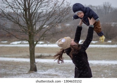 happy young mother is catching her flying adorable smiling son babyboy above her head with snowy landscape in the background