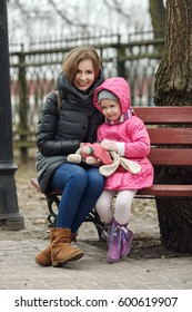 Happy young mother and child daughter hugging sitting on bench in spring park