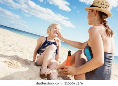 happy young mother and child in swimsuit on the seashore applying sun screen
