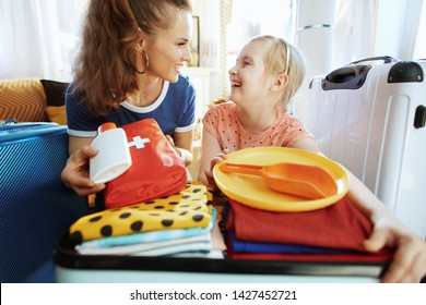 happy young mother and child travellers with open suitcase suitcase ready for resort at modern home in sunny summer day.