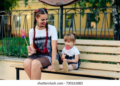 happy young mother with a cute daughter on a bench with a lollipop in hands in identical dresses