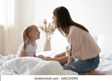 Happy young mother and cute small preschooler daughter sit in bed talking chatting sharing secrets, smiling mom and little girl child have fun playing in bedroom enjoy free time at home together