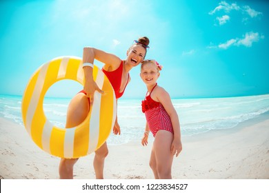 happy young mother and daughter in red beachwear with yellow inflatable lifebuoy on the beach